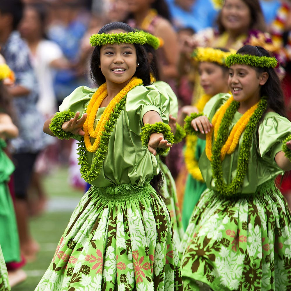 girl s in green dress dancing during daytime with leis
